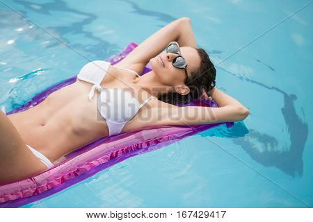 Attractive young woman relaxing on inflatable raft at swimming pool