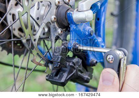 Mechanic serviceman installing adjusting bicycle gear on wheel