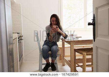 View from doorway of girl messaging on smartphone in kitchen