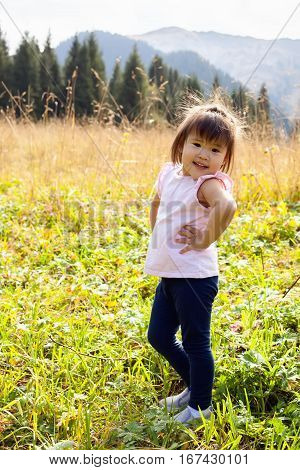 Little asian girl walking on meadow with mountains in the background