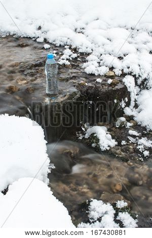 A bottle of mineral water is in the source of spring water.