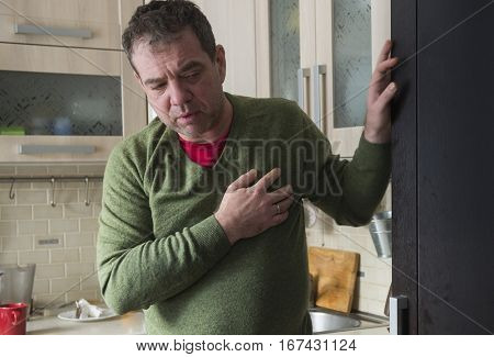 Heart attack. Mature man in home clothes holding her hand to her heart. His face was red. Selective focus on hand.