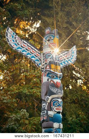 Indian totem poles with sun ray in Stanley park in Vancouver, Canada.