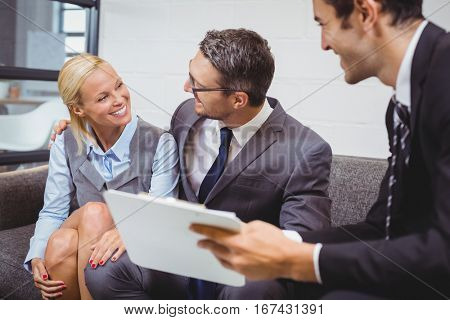 Smiling businesman with clients sitting on sofa in office