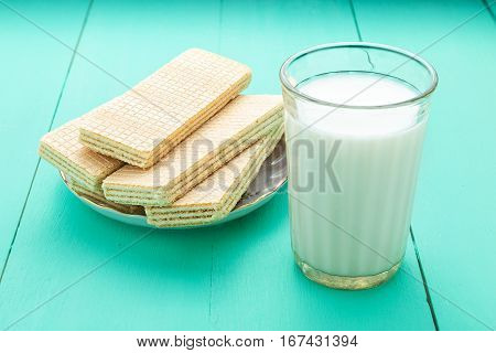 sweet crunchy waffles and milk in a glass on a blue wooden background. tasty breakfast