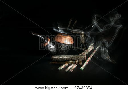 Pipe with a pipe-lighter and smoking accessories on a black background