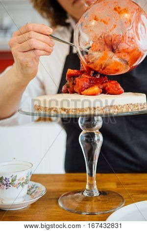 Close up of unrecognizable confectioner decorating cake with fresh strawberry