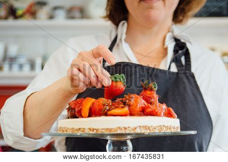 Unrecognizable baker woman decorating cake with strawberry