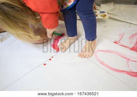 Three years blonde child barefoot with red bib and blue trousers with brush painting with red watercolor on white paper in the floor