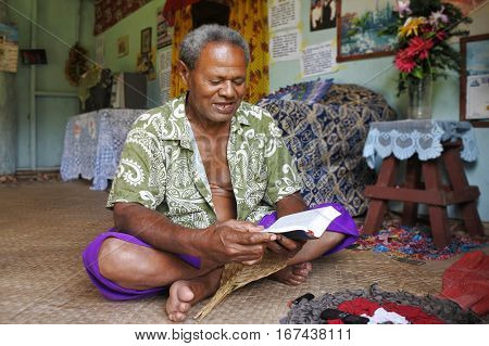 Indigenous Fijian man reads the bible in his home in Fiji. Fiji was Christianized in the 19th century. Today there are various Christian denominations in Fiji the majority being Methodist.