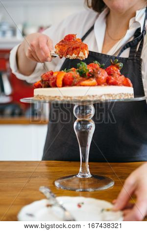 Unrecognizable confectioner serving piece of strawberry cake on plate