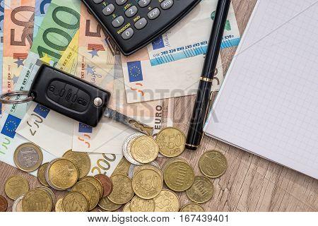 car key euro banknotes pen coins and notebook