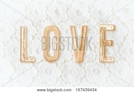 Top view or Flat lay of Golden word love on white lace with small flowers on the white background. Valentines Day love or wedding day concept.