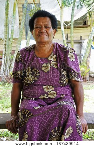 Elderly indigenous Fijian woman in her 70's sit outside her village home. Real people copy space