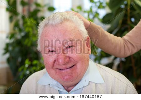 Picture of a smiling elderly man at home with his caregiver