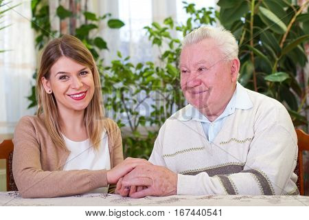 Picture of an elderly man with cheerful caregiver