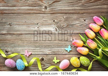 Easter background with colorful eggs, spring tulips and ribbon. Top view with copy space