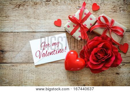 Red hearts, rose, message card and gift boxes on wooden table. Valentines Day background