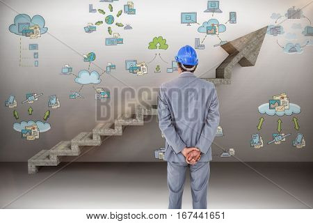 Businessman with helmet turning his back to camera against digital composite image of gray steps moving up