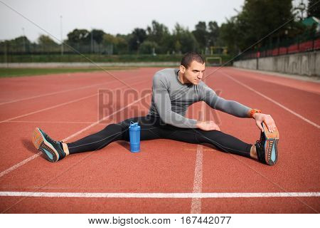 Athlete warming and stretching. Sitting on the track while having a drink of water.