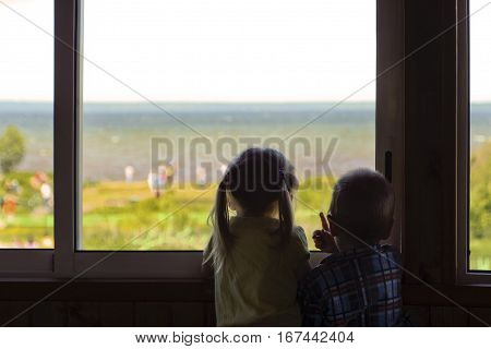 Two small children boy and girl look at the water and people from the window of the room in the summer.