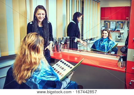 beauty hair dyeing and people concept - happy young woman with hairdresser choosing hair color from palette samples at salon