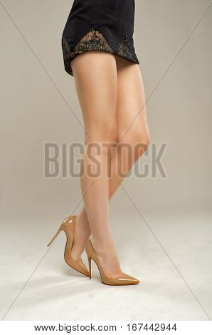 Beautiful girl's legs in patent leather shoes isolated on beige background