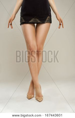 long smooth legs girls patent leather shoes isolated on beige background