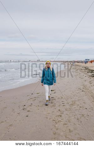 young woman traveler walking along the beach in winter. woman in a blue jacket and yellow knitted cap walking on the beach on the background stormy sea