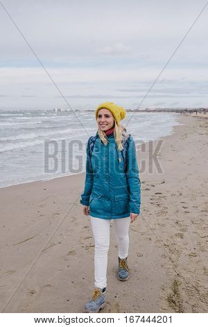 young woman traveler walking along the beach in winter. smiling woman in a blue jacket and yellow knitted cap walking on the beach on the background stormy sea