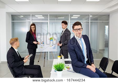 Young businessman wearing glasses on the background of her colleagues in a modern office.