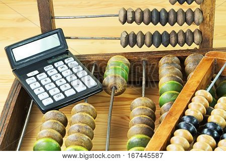 Old wooden abacus and the calculator on a wooden background