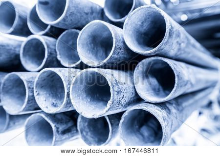 Low Depth Of Field Image Of Metal Pipe Stack In Blue Shade Tone. Rounded Iron Pipe Shape.