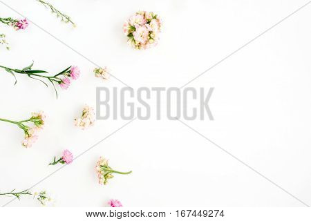 Floral background with pink and beige wildflowers green leaves branches on white background. Flat lay top view. Valentine's background