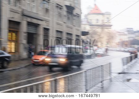 cars going down the street in the rain. blurred focus.