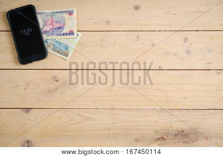 Banknotes of Nigerias on the wooden table under the smartphone