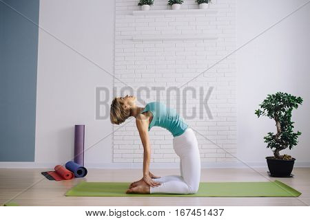 young girl in a blue t-shirt doing yoga at home. wellness concept