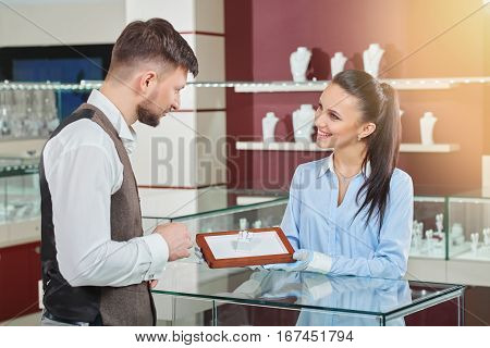 Side view of handsome man choosing jewelry for girlfriend. Female jeweler in gloves showing  box with engagement ring with blue stone. Looking each other, talking and smiling. Jewelry luxury store.