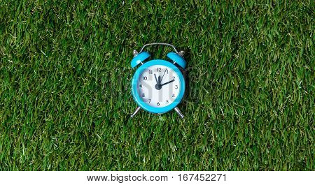 Blue Little Retro Alarm Clock On Green Grass Background, Above View