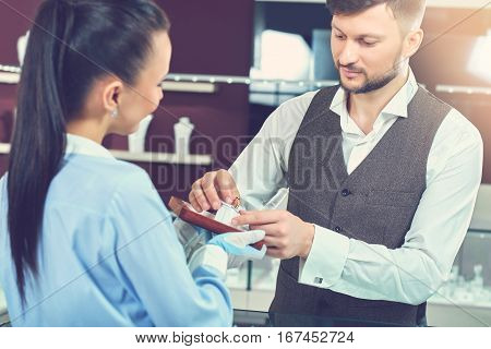 Portrait of handsome brunet man with beard choosing present for his girlfriend and holding ring with blue stone in hands. Jeweler in gloves showing box with engagement ring and smiling to buyer.