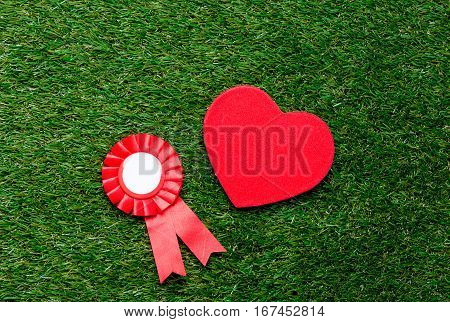 Little Red Winner Award And Heart Shape Gift On Green Summer Grass Lawn