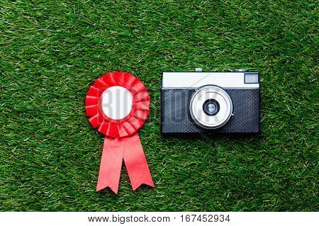 Red Reward And Vintage Camera On Green Grass Background