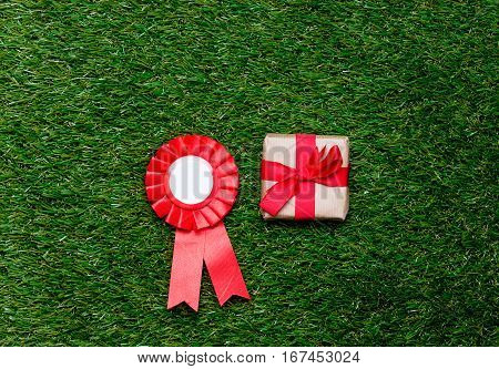 Red Reward And Gift Box On Green Grass Background,