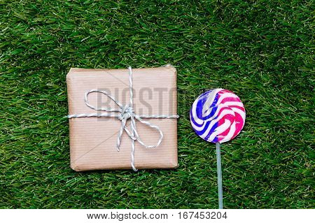 Gift Box And Lollipop Candy On Green Grass Background, Above Point Of View