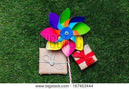 Pinwheel Toy And Two Gift Boxes On Green Grass Background, Above Point Of View