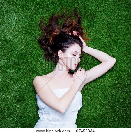 Portrait Of A Young Redhead Woman Lying Down On Green Spring Grass, Above Point Of View