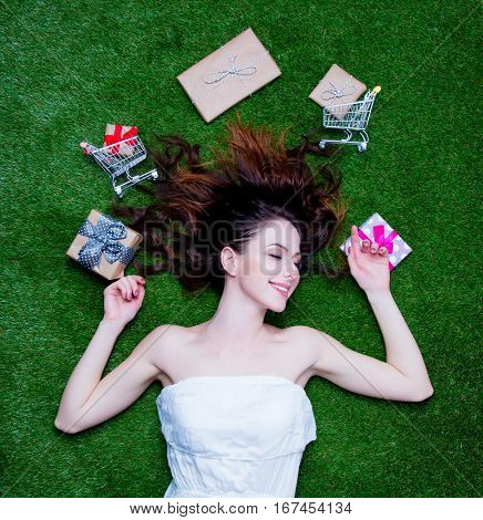 Portrait Of A Young Surprised Redhead Woman With Holiday Gifts And Shopping Carts Lying Down On Gree