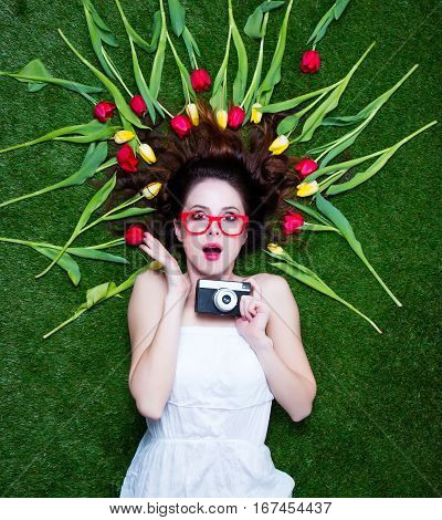 Portrait Of A Young Redhead Woman With Camera And Tulips