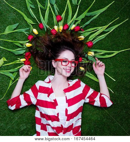 Portrait Of A Young Styled Redhead Woman Tulips Around And Glasses Lying Down On Green Spring Grass,