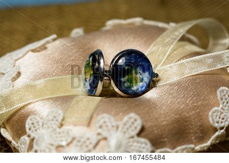 silver cufflinks with a picture of the earth